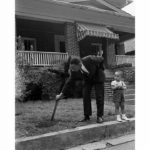 pulls up a burnt cross from his front lawn while his son looks on - 1960.      ...